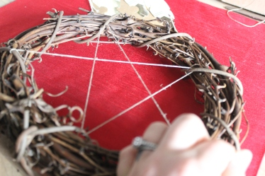 Lace twine back and forth (creating a star-like pattern), on the back side of your wreath.